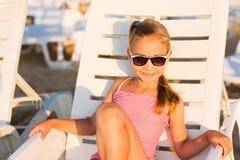 Adorable kid sunbathing on a beach Stock Photos
