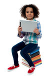 Adorable kid with tablet pc sitting on books Royalty Free Stock Photos