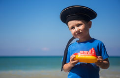 Adorable kid with toy boat against the sea on sunny day Stock Photography