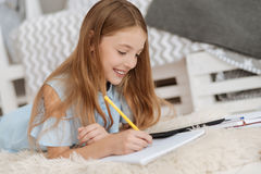 Adorable kid writing in notebook while studying at home Royalty Free Stock Photos