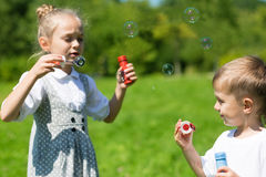 Adorable kids blow bubbles outdoors Stock Photo