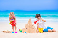 Adorable kids building sand castle on a beach. Kids playing on a beach. Two children build a sand castle at the sea shore. Family vacation on a tropical island royalty free stock image