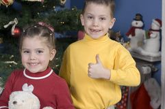Adorable kids with the Holiday Spirit. Iin front of a Christmas tree, boy stands with thumbs up by his sister who is holding a teddy bear Stock Photo