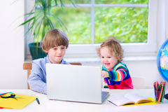 Adorable kids with a laptop Stock Images