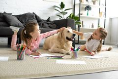 Adorable kids petting golden retriever dog while drawing pictures on floor. At home stock images