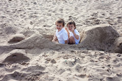 Adorable kids, playing on the beach with car, made of sand stock photography