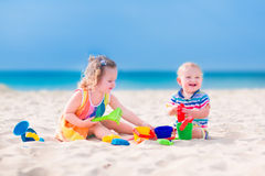 Adorable kids playing on the beach Stock Photos