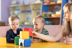 Adorable kids playing with constructor on table in kindergarten stock photo