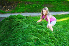 Adorable kids playing with cutted grass royalty free stock photos