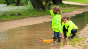 Adorable Kids Playing In Huge Puddle After Rain stock footage