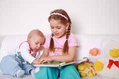 Adorable kids reading and playing stock photo
