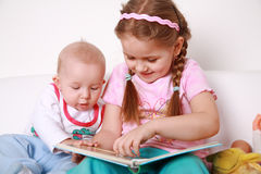 Adorable kids reading and playing Royalty Free Stock Images