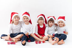 Adorable kids with santa hats, smiling at the camera Stock Photos