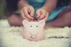 Adorable kids saving coins in piggy bank. Happy little investment saving money for happiness future. Girls smiling with happy. Face royalty free stock photography
