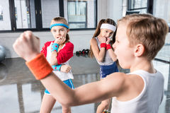 Adorable kids in sportswear fooling around at fitness studio. Children sport concept stock photography