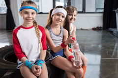 Adorable kids in sportswear sitting on tire at fitness studio. Children sport concept royalty free stock image