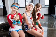 Adorable kids in sportswear sitting on tire at fitness studio. Children sport concept royalty free stock photo