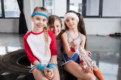 Adorable kids in sportswear sitting on tire at fitness studio. Children sport concept royalty free stock photography