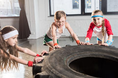 Adorable kids in sportswear training with tire at fitness studio. Children sport concept stock image