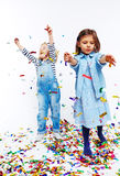 Adorable Kids Throwing Confetti. Studio portrait of two little girls both dressed in blue jeans clothes having fun with confetti, throwing it around against Stock Photo