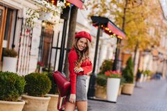 Adorable lady in short gray skirt looking back over shoulder and smiling. Outdoor portrait of playful french girl in red