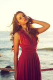 Adorable lady. Young beautiful elegant woman in pink dress standing near sea Royalty Free Stock Photography