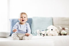 Adorable laughing baby boy sitting on sofa and looking up. Royalty Free Stock Photos