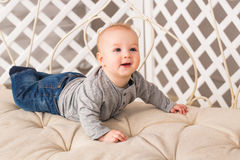 Adorable laughing baby boy in sunny bedroom. Newborn child relaxing. Family morning at home. Little kid lying on tummy Royalty Free Stock Image