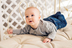 Adorable laughing baby boy in sunny bedroom. Newborn child relaxing. Family morning at home. Little kid lying on tummy stock image