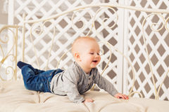 Adorable laughing baby boy in sunny bedroom. Newborn child relaxing. Nursery for young children.Family morning at home Stock Photography