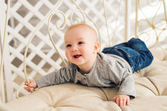 Adorable laughing baby boy in sunny bedroom. Newborn child relaxing. Nursery for young children.Family morning at home Stock Image