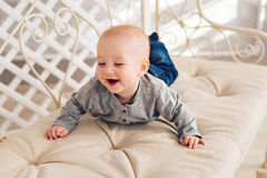 Adorable laughing baby boy in sunny bedroom. Newborn child relaxing. Nursery for young children.Family morning at home Royalty Free Stock Photography