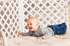 Adorable laughing baby boy in sunny bedroom. Newborn child relaxing. Nursery for young children.Family morning at home Royalty Free Stock Image