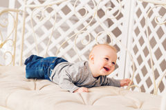 Adorable laughing baby boy in sunny bedroom. Newborn child relaxing. Nursery for young children.Family morning at home Royalty Free Stock Photo