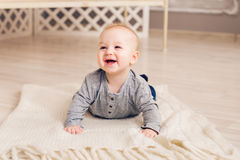 Adorable laughing baby boy in white sunny bedroom. Newborn child relaxing. Family morning at home. Royalty Free Stock Photos