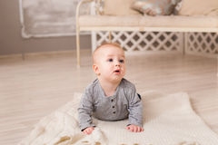 Adorable laughing baby boy in white sunny bedroom. Newborn child relaxing. Family morning at home. Royalty Free Stock Images