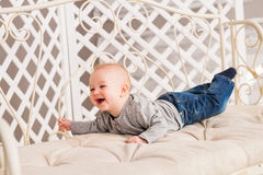 Adorable laughing baby boy in white sunny bedroom. Newborn child relaxing. Family morning at home. Stock Photos