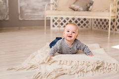 Adorable laughing baby boy in white sunny bedroom. Newborn child relaxing. Family morning at home. Stock Photo