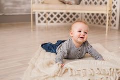 Adorable laughing baby boy in white sunny bedroom. Newborn child relaxing. Family morning at home. Royalty Free Stock Photo