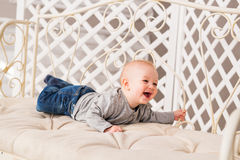 Adorable laughing baby boy in white sunny bedroom. Newborn child relaxing. Family morning at home. Stock Images