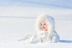Adorable laughing baby girl in snowy park Stock Image