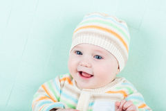Adorable laughing baby wearing a warm knitted jack Royalty Free Stock Photo