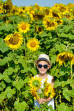 Adorable laughing blond boy in sun glasses and hat with sunflower on field outdoors. Kids portrait. Summer countryside agriculture Stock Photo