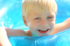 Adorable Laughing Blonde Kid Playing in Swimming Pool Stock Photo