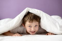 Adorable laughing boy playing in bed under a white blanket or coverlet Royalty Free Stock Photo
