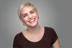 Adorable laughing lady head shot short pixie haircut modern style gray background Royalty Free Stock Photo