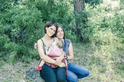 Adorable lesbian couple with their baby girl in nature. Royalty Free Stock Photo