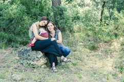 Adorable lesbian couple with their baby girl in nature. Royalty Free Stock Image