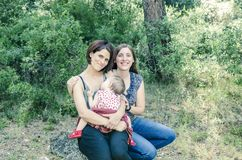 Adorable lesbian couple with their baby girl in nature. Stock Photos