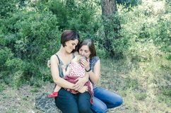 Adorable lesbian couple with their baby girl in nature. Stock Photography